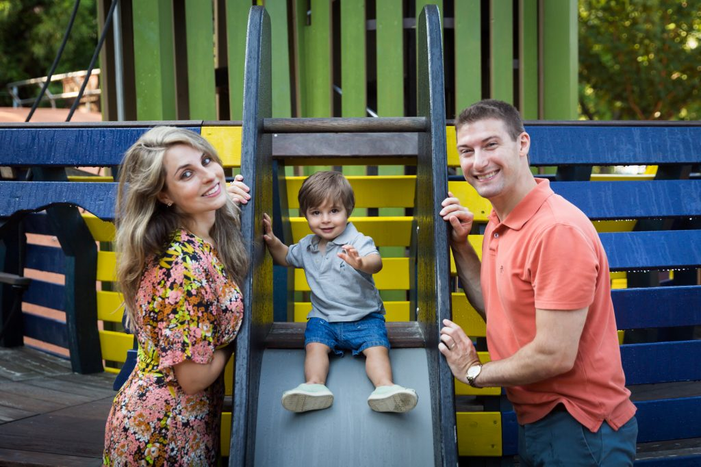 Parents with little boy on slide during a Chelsea Waterside Park family portrait session