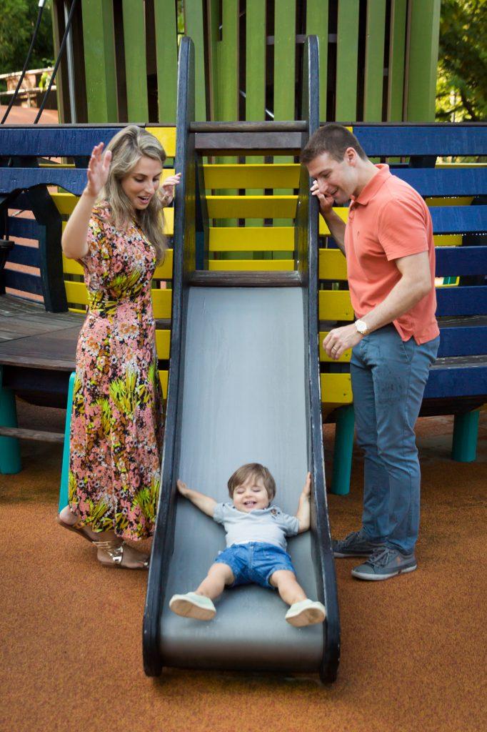 Parents watching little boy go down slide during a Chelsea Waterside Park family portrait session