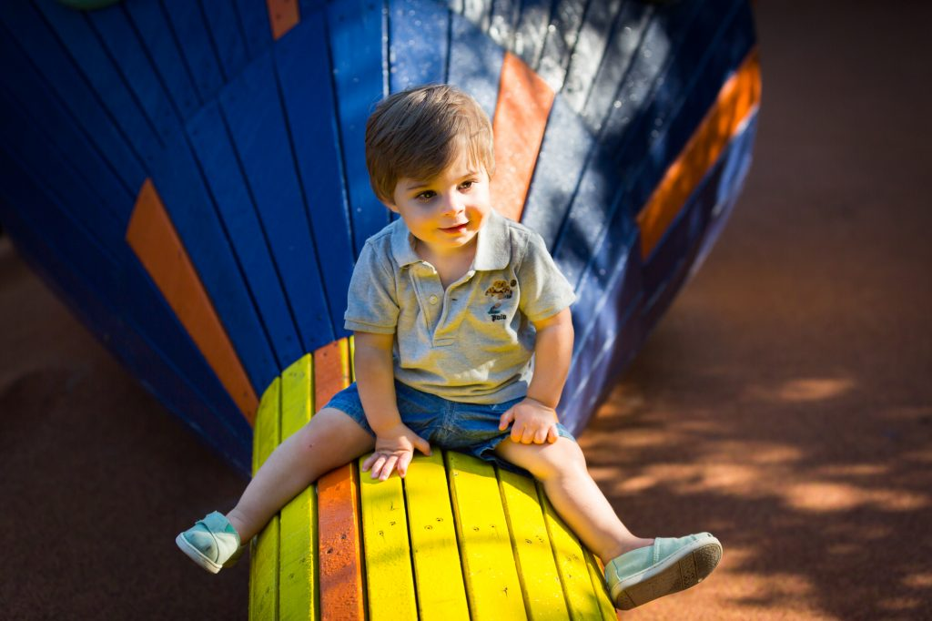 Little boy sitting on blue and yellow wooden snake during a Chelsea Waterside Park family portrait session