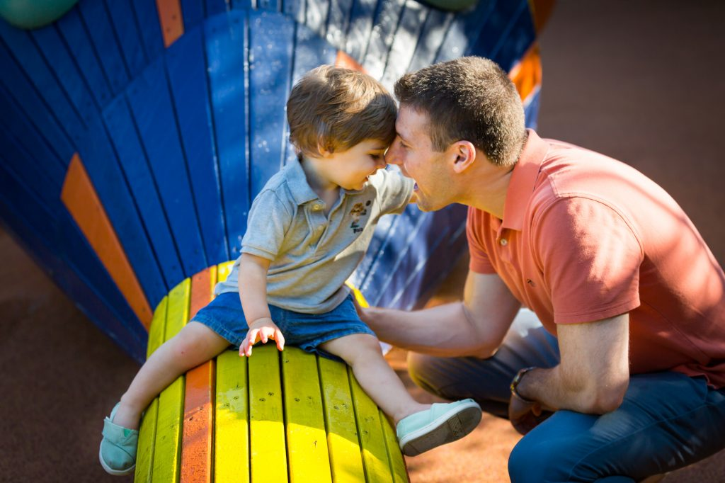 Little boy and father sitting on blue and yellow snake during a Chelsea Waterside Park family portrait session