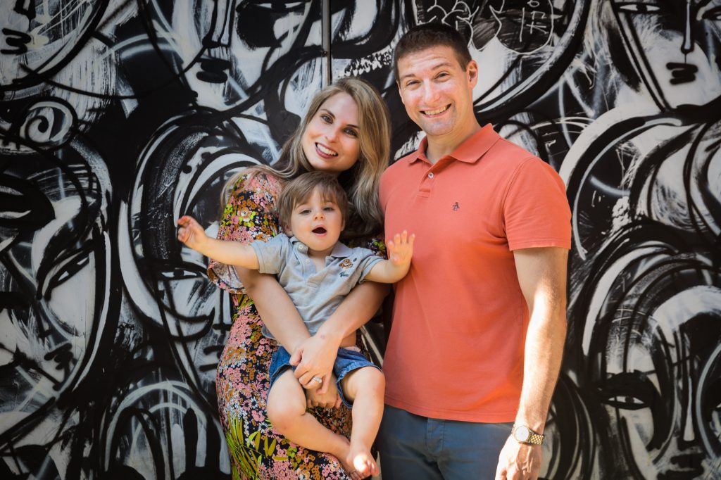 Parents with little boy in front of black and white graffiti wall