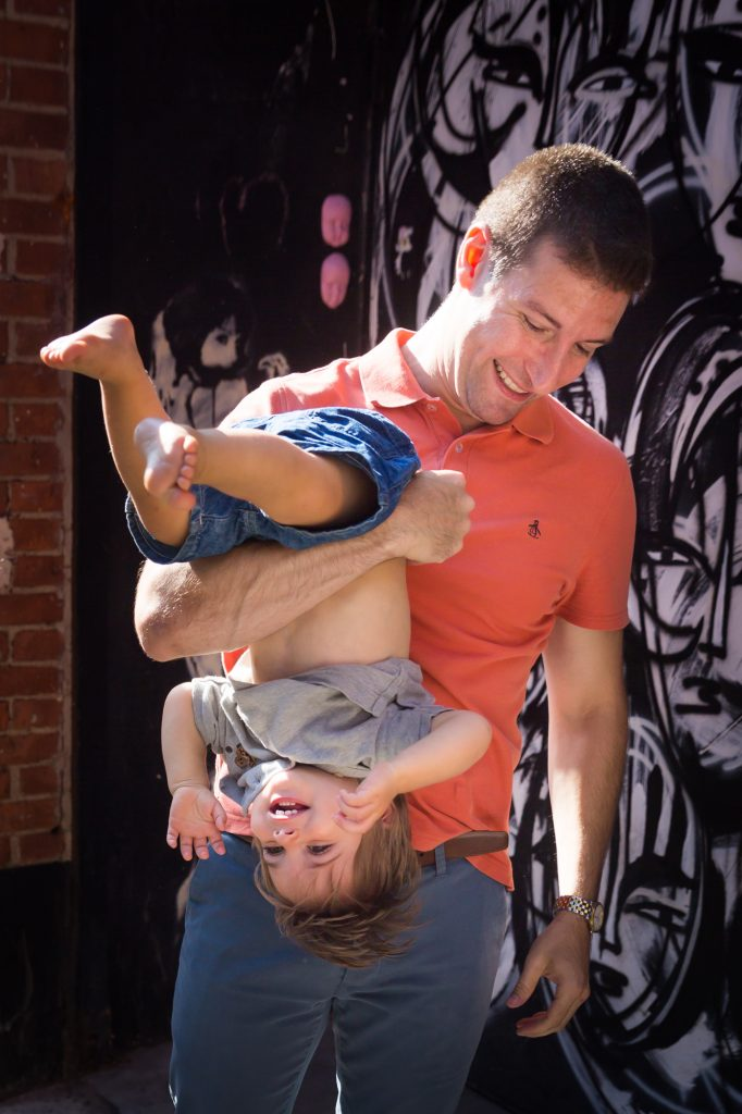 Father holding son upside down in front of black and white graffiti wall