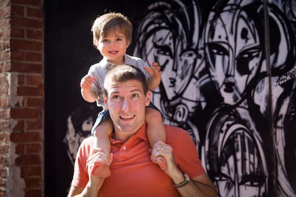 Father with son on shoulders in front of black and white graffiti wall