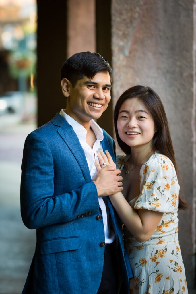 Couple holding hands by column during Queens engagement photo session