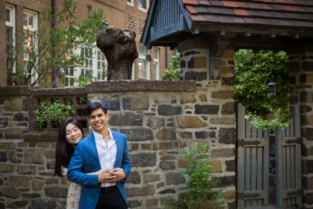 Couple hugging in front of stone wall and small gate during Forest Hills engagement shoot