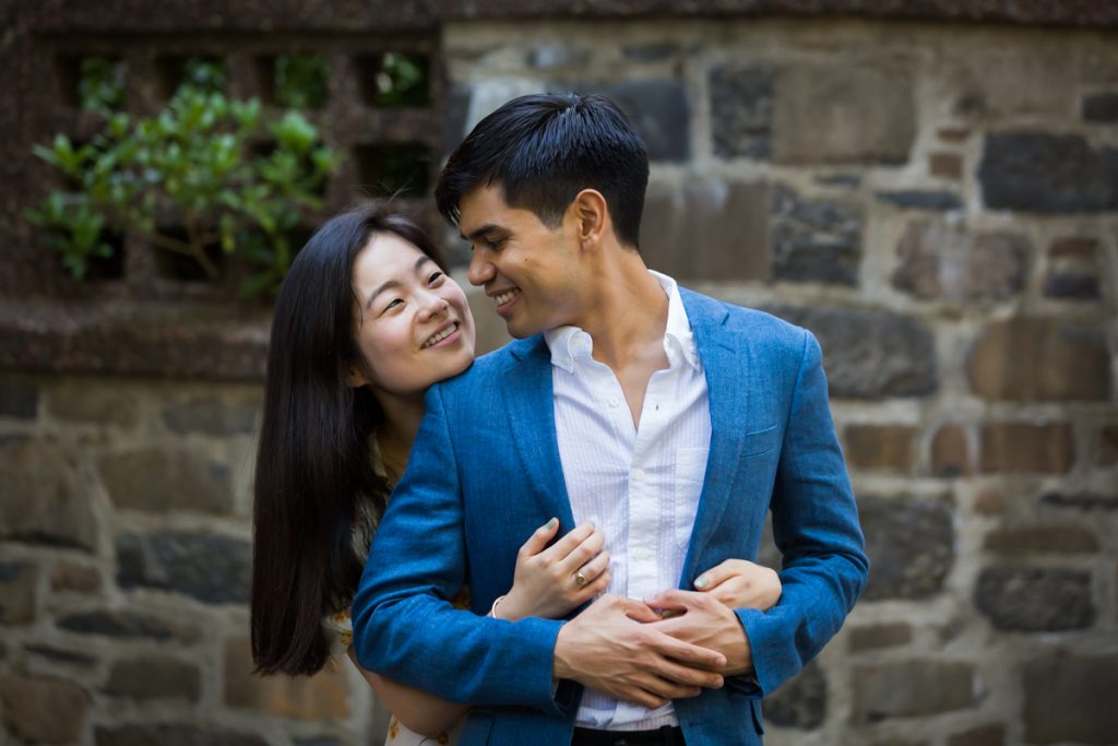 Couple hugging in front of stone wall during Queens engagement photo session