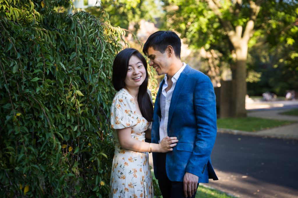 Couple in front of bush on Greenway Terrace during Forest Hills engagement shoot