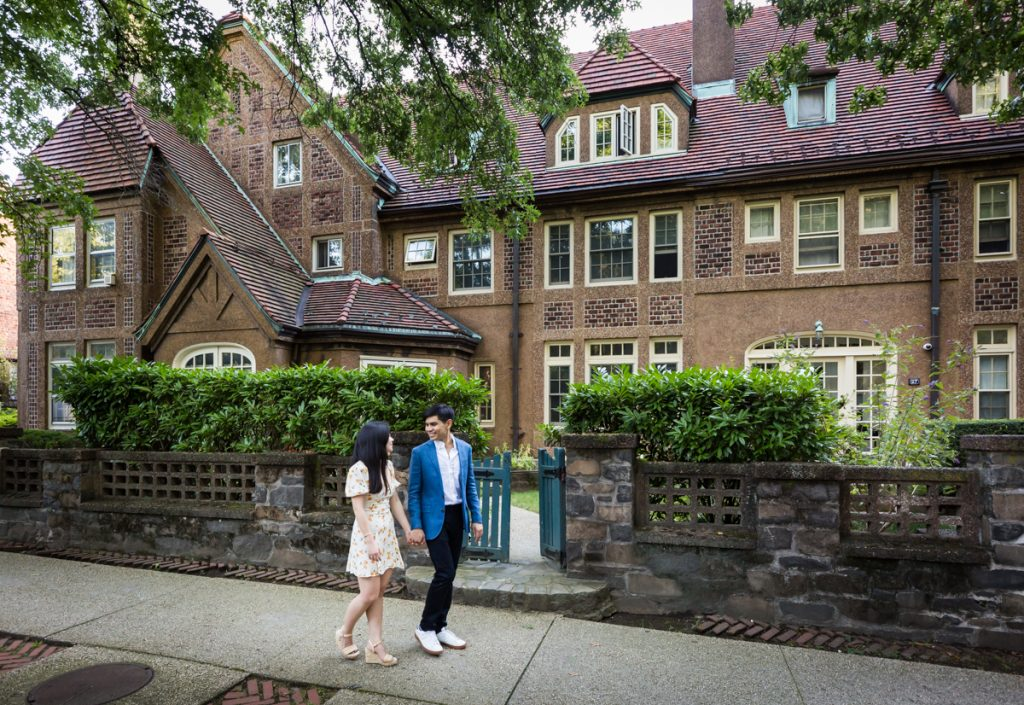 Couple walking past Tudor-style home during Forest Hills engagement shoot