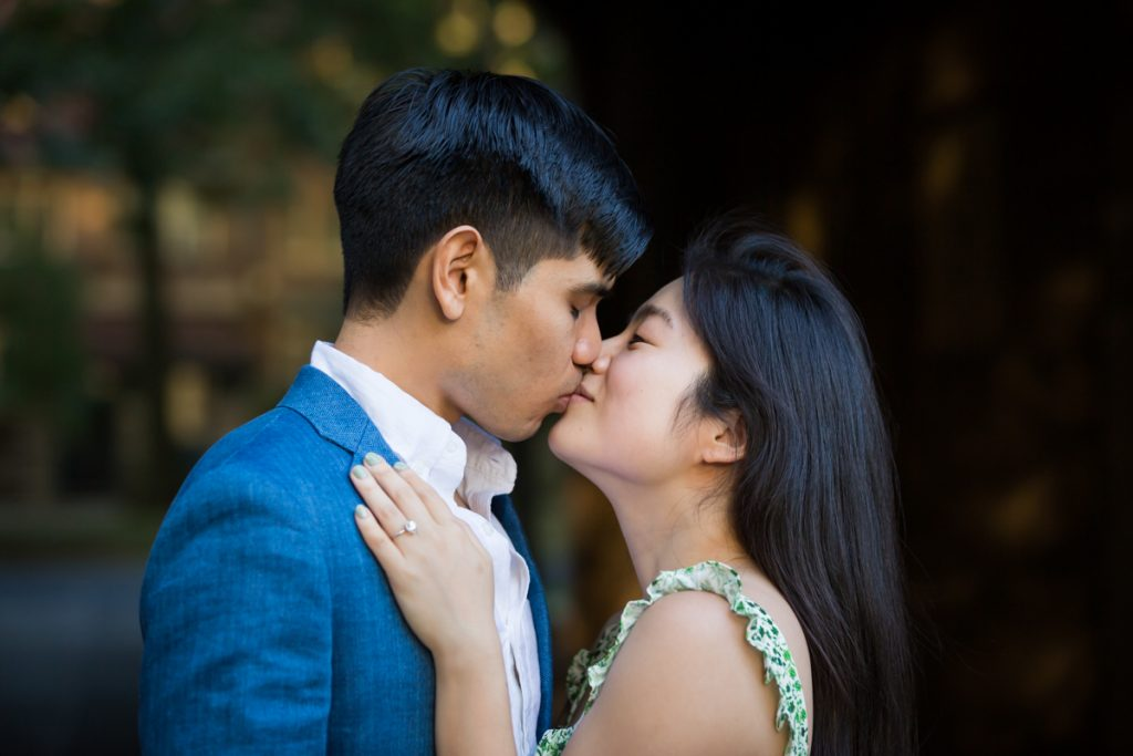 Couple kissing in dark archway during Forest Hills engagement session