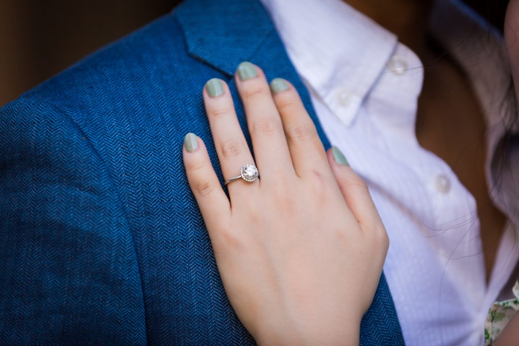 Close up of woman's hand wearing engagement ring on man's jacket lapel