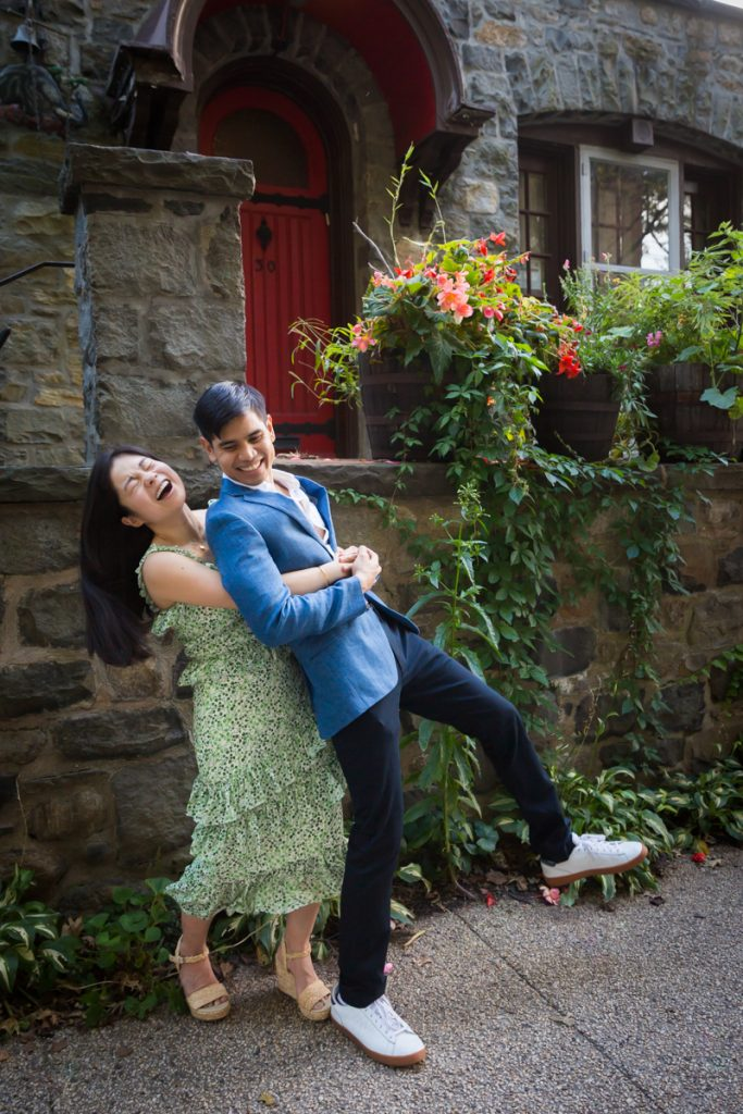 Woman lifting man up during Forest Hills engagement shoot