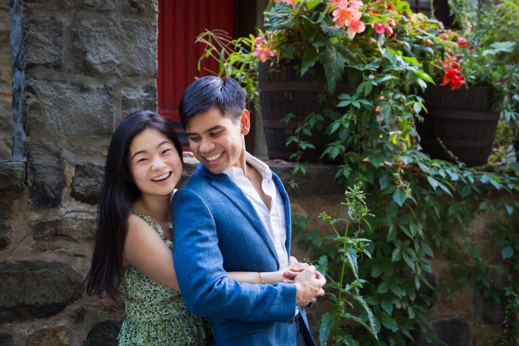 Couple hugging in front of vine-covered wall during Forest Hills engagement shoot