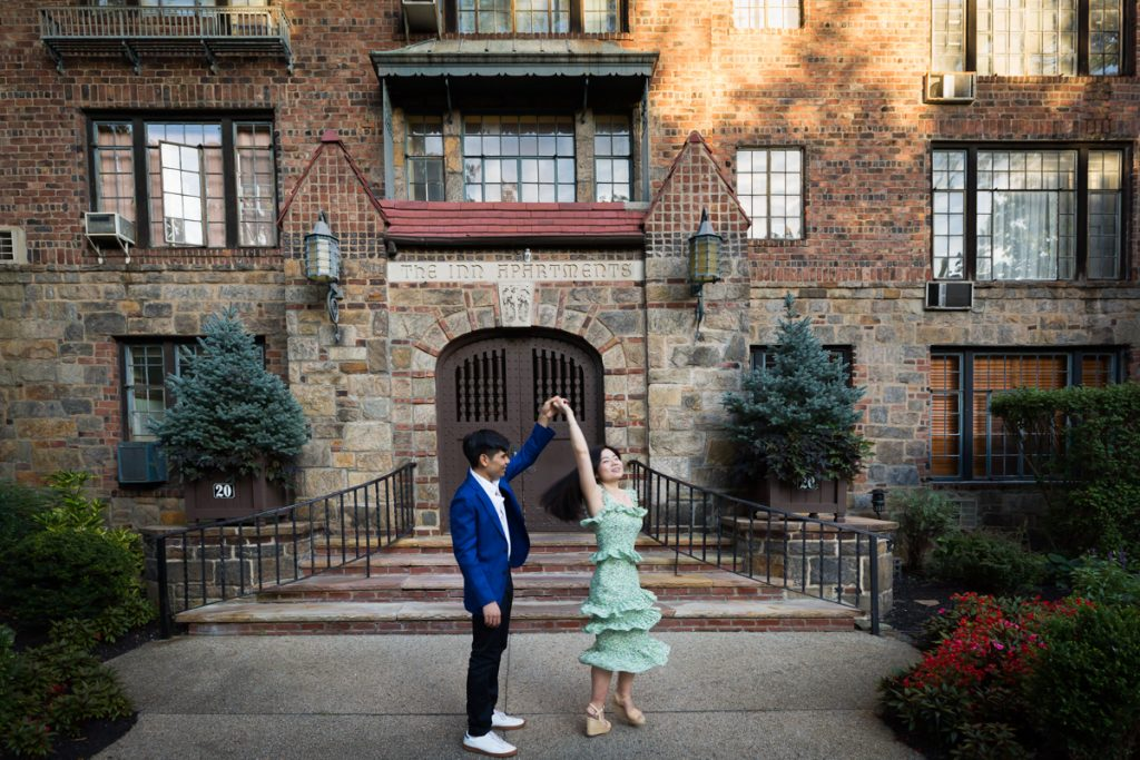 Couple dancing in front of Forest Hills Inn Apartments during Forest Hills engagement shoot