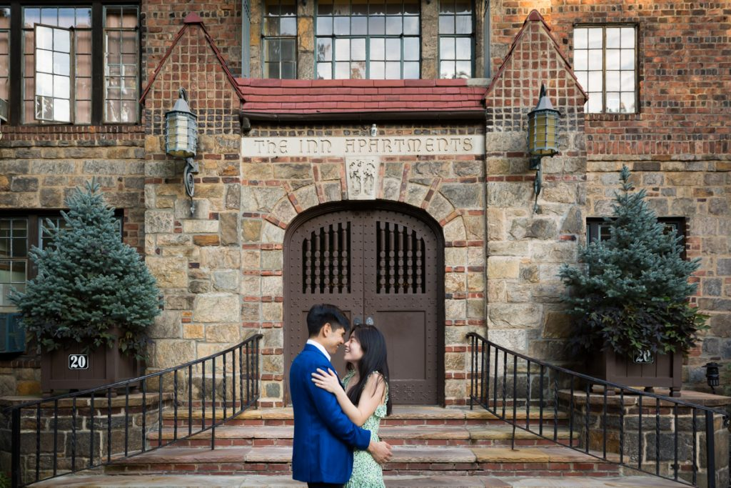 Couple hugging in front of steps of Forest Hills Inn Apartments