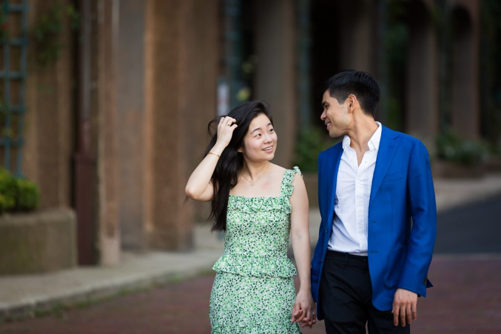 Woman touching hair while walking with man during Forest Hills engagement session