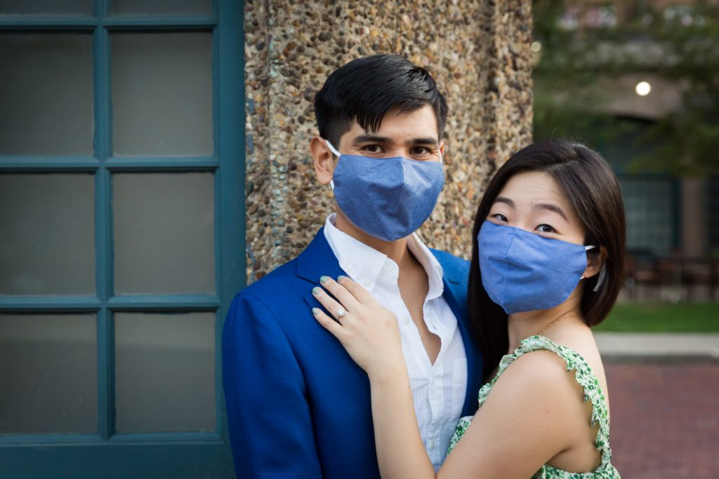 Couple wearing blue masks hugging during Forest Hills engagement shoot