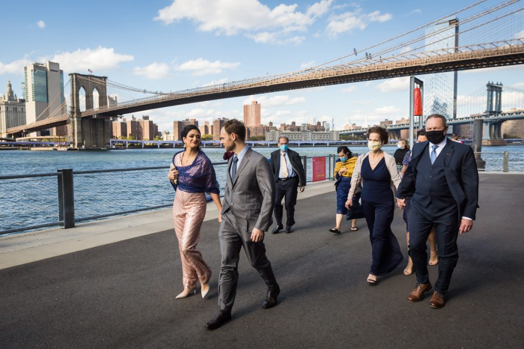 Bride and groom leading family through Brooklyn Bridge Park