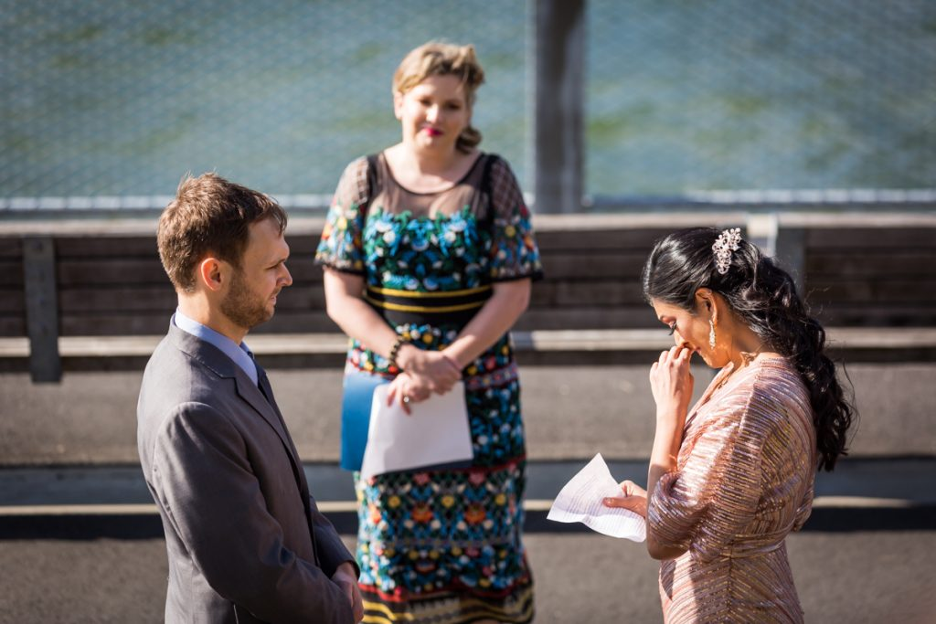 Bride crying during vows at a during Brooklyn Bridge Park wedding ceremony
