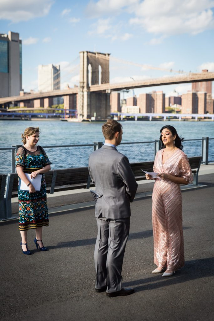 Bride and groom saying vows in front of Brooklyn Bridge