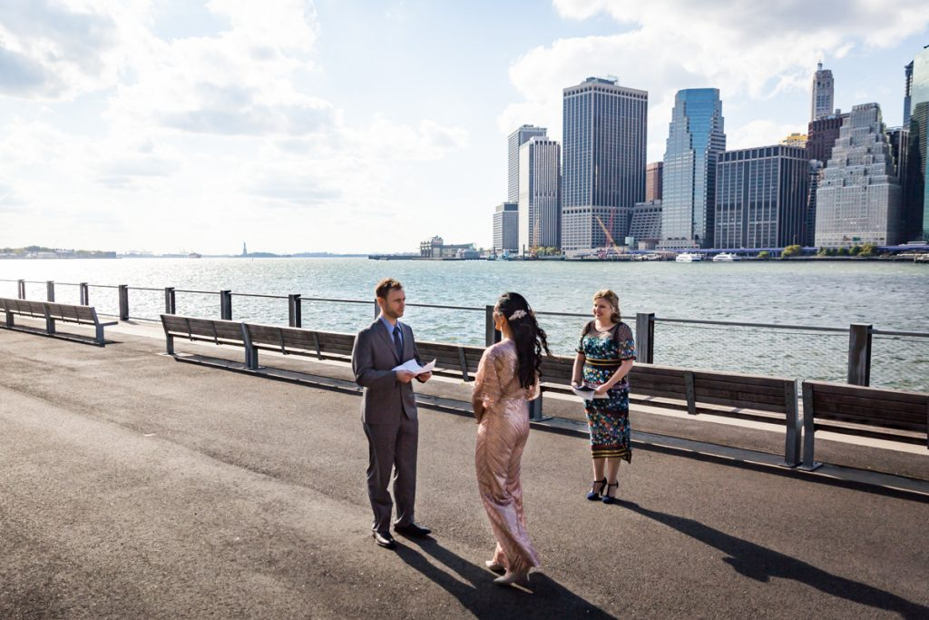 Bride and groom saying vows in front of NYC skyline for an article on how to get married in Brooklyn Bridge Park
