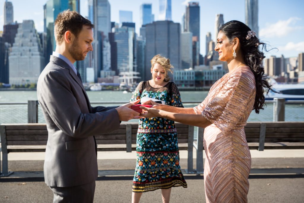 Bride and groom swapping ring boxes during Brooklyn Bridge Park wedding ceremony