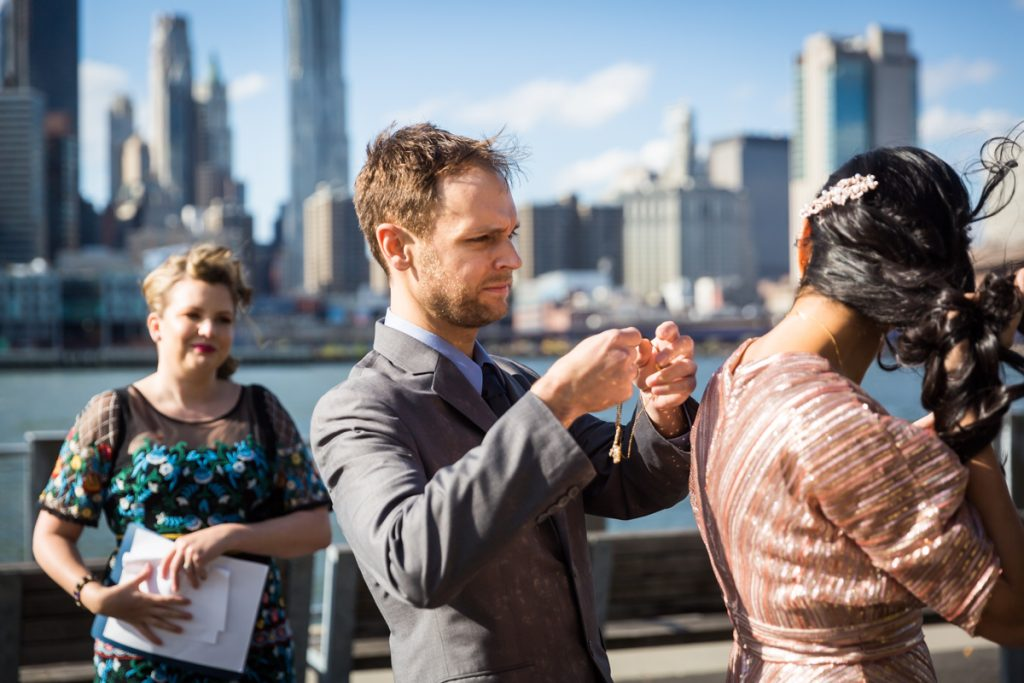 Groom putting necklace on Indian bride during Brooklyn Bridge Park wedding