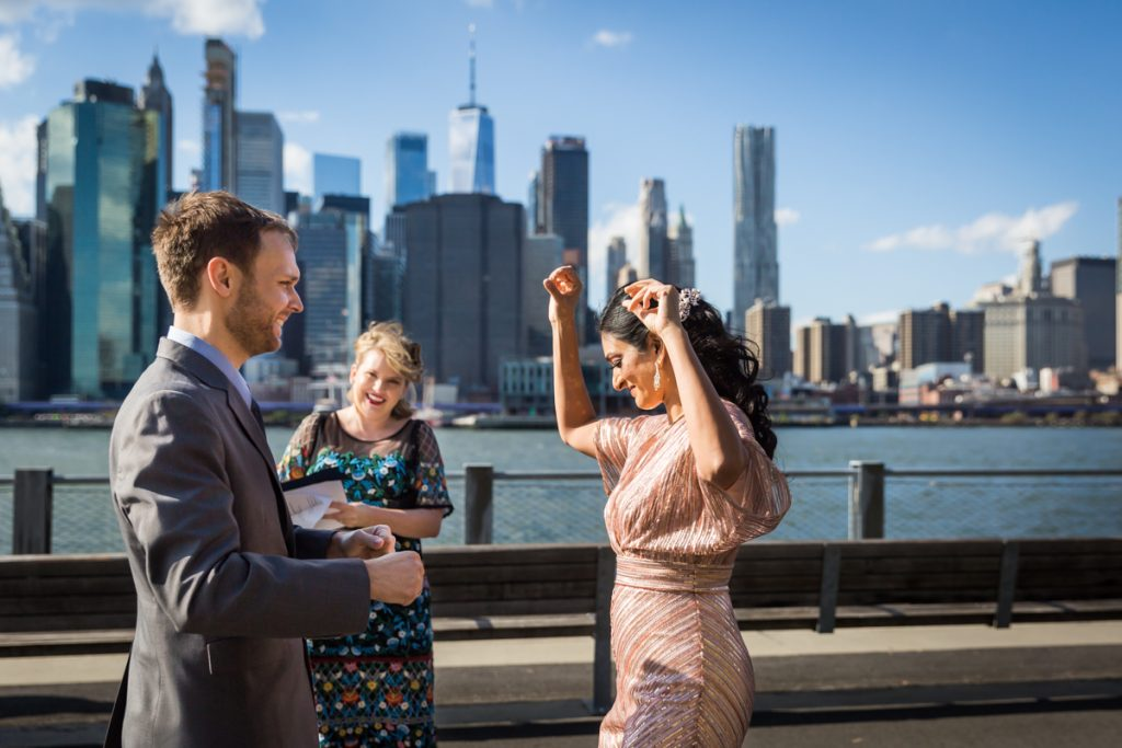 Groom watching bride dance for an article on how to get married in Brooklyn Bridge Park