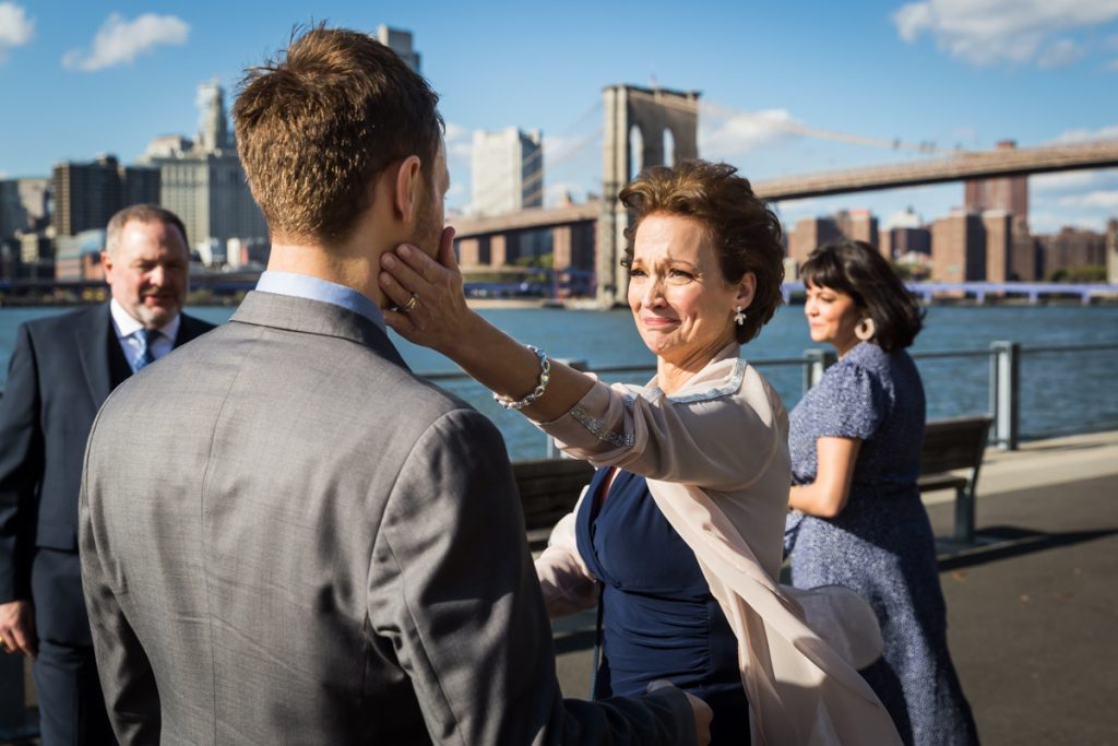 Mother touching son's cheek during Brooklyn Bridge Park wedding ceremony
