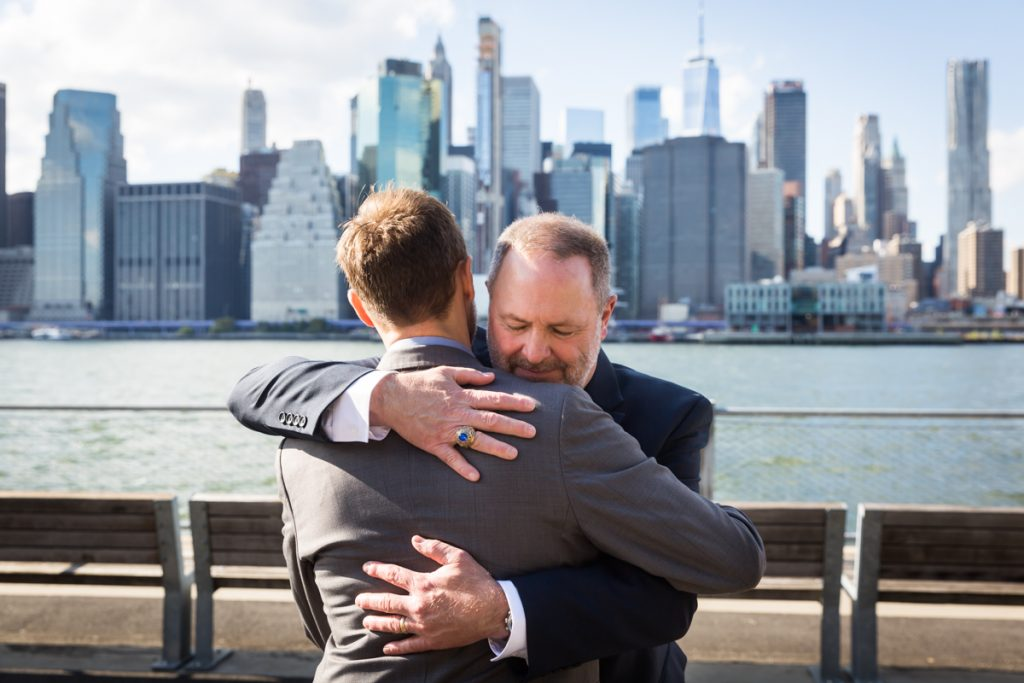 Father hugging groom during Brooklyn Bridge Park wedding ceremony