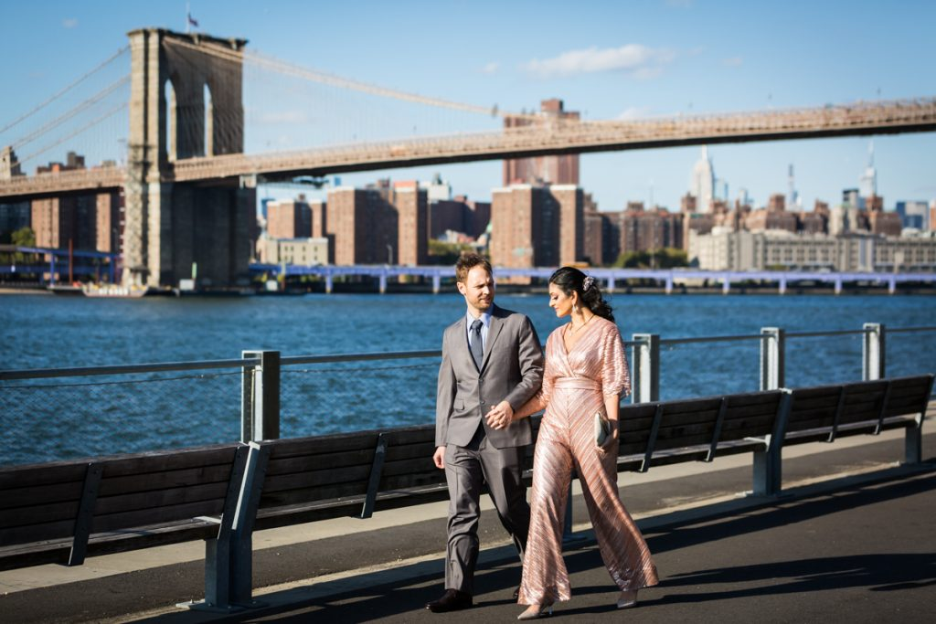 Bride and groom walking with Brooklyn Bridge in background