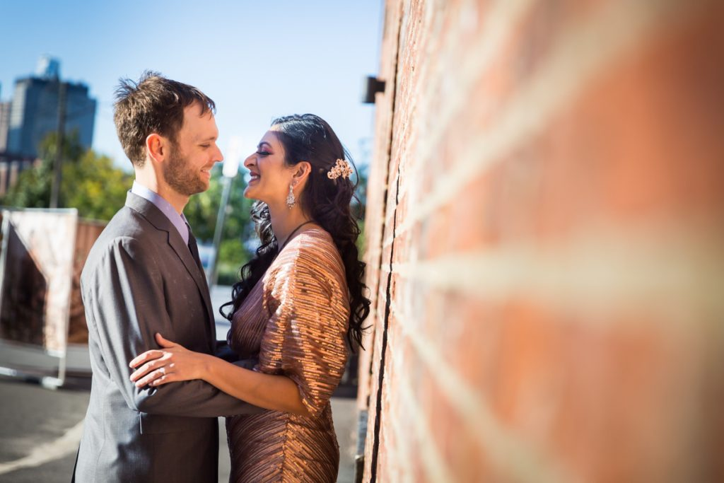 Bride and groom leaning against brick wall