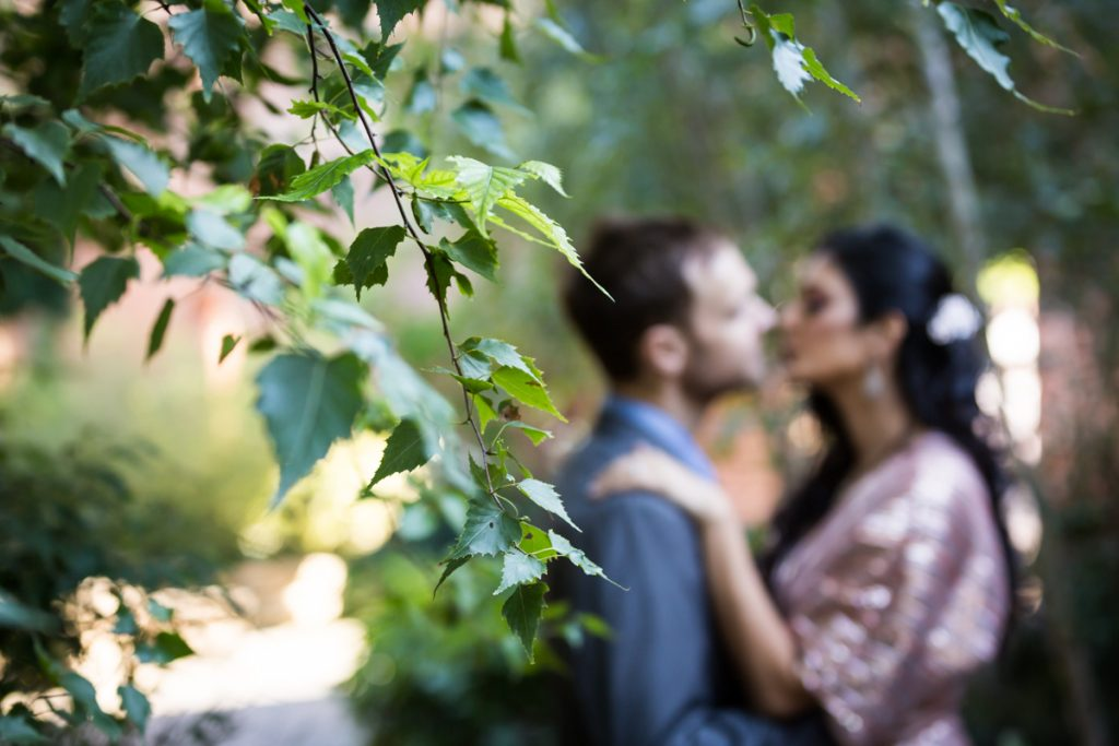 Bride and groom kissing behind branch in Max Family Garden