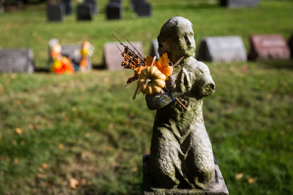 Grave statue holding fall pumpkin decoration