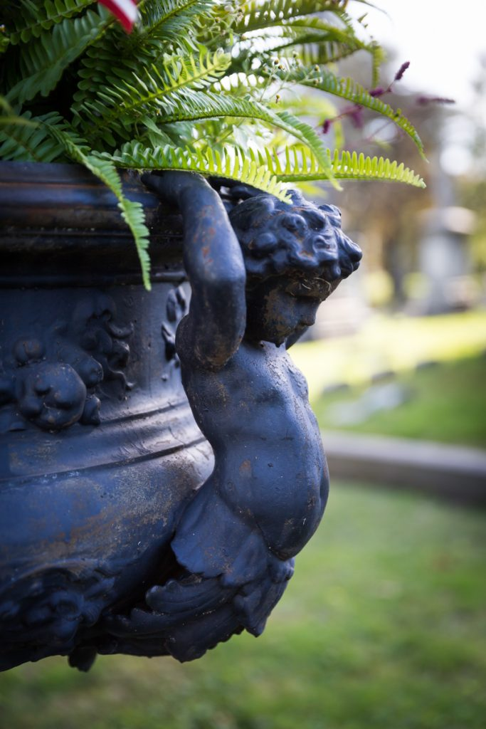 Cherub holding up plant urn at Green-Wood Cemetery