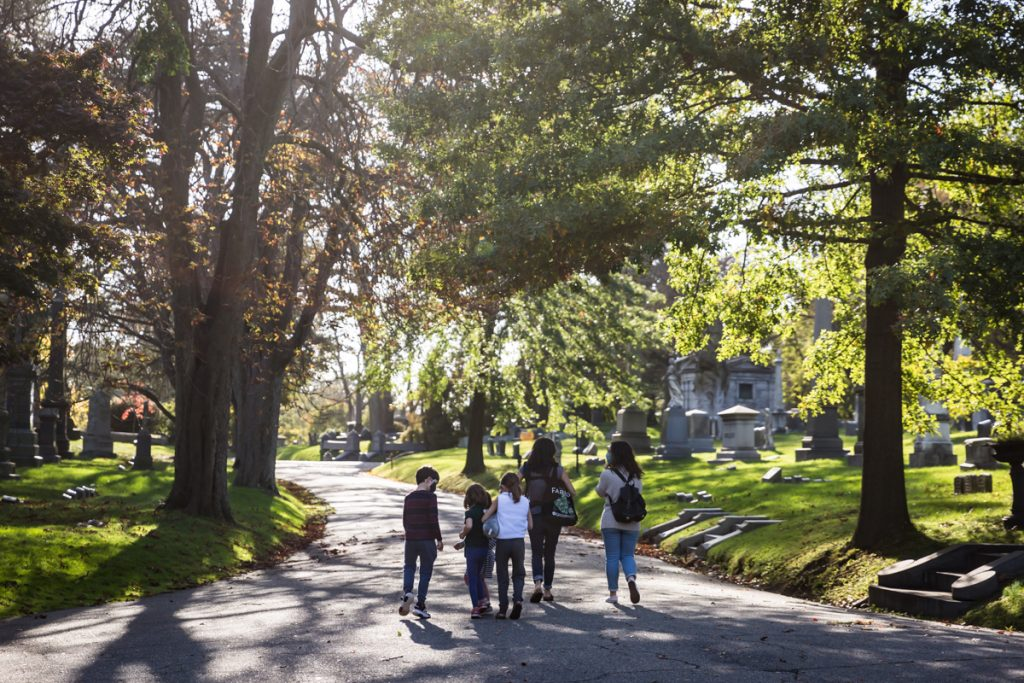 Moms and kids walking along pathways for an article on visiting Green-Wood Cemetery