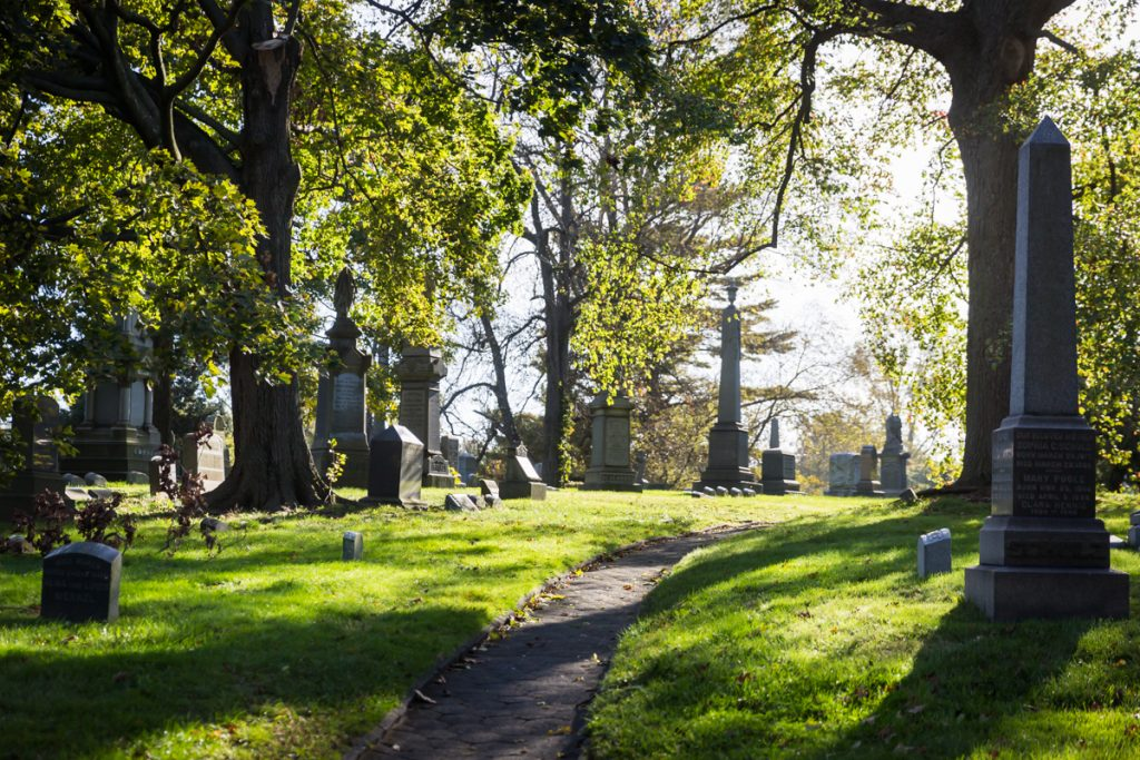 Graves and sunlit pathway at Green-Wood Cemetery
