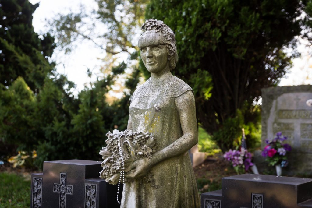 Statue of woman holding flowers at Green-Wood Cemetery