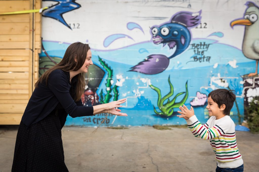 Mother and son playing shark in front of colorful mural