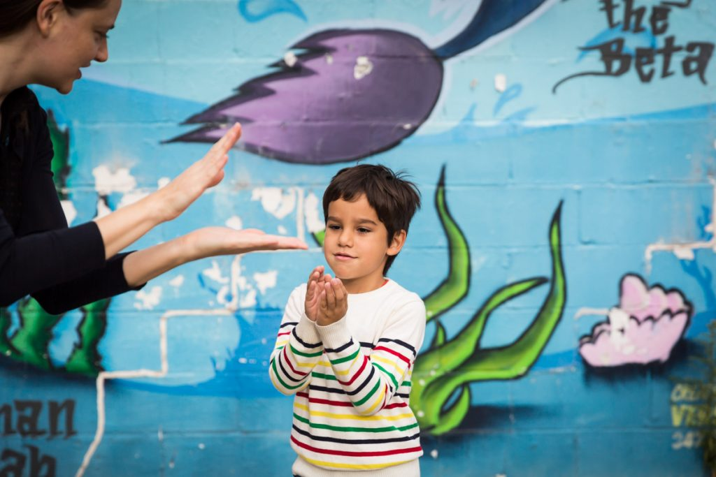 Boy standing in front of colorful mural in Gowanus