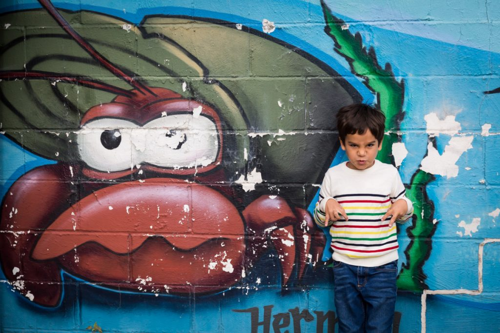 Little boy making crab face in front of colorful sea life mural