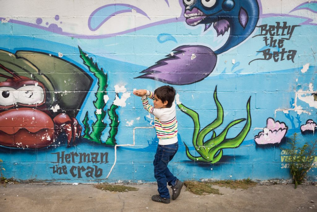 Little boy playing shark in front of ocean life mural