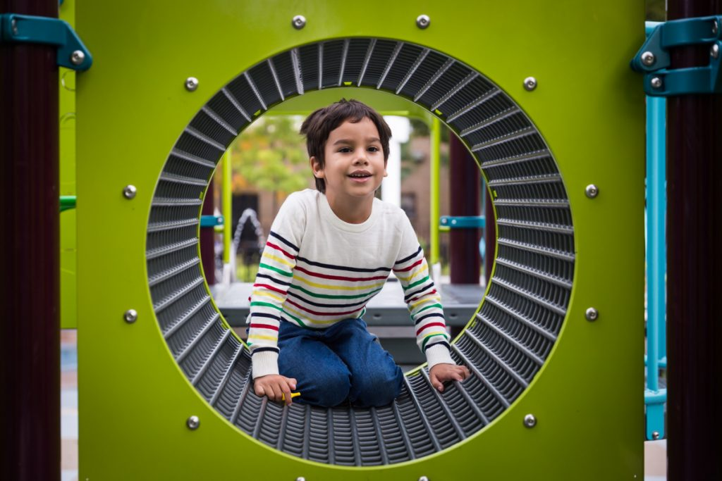 Little boy looking through green tunnel during a Gowanus family portrait session
