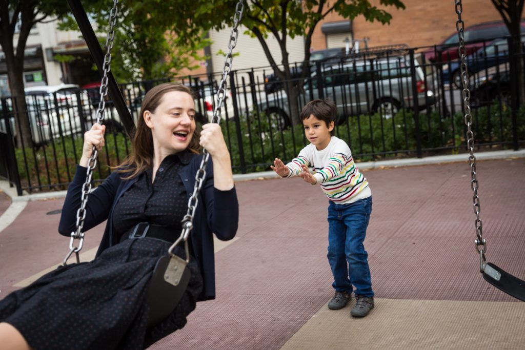 Boy pushing mother in swing during a Gowanus family portrait session