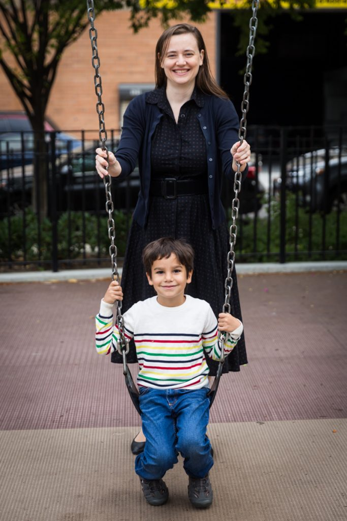Mother standing over boy on swings during a Gowanus family portrait session