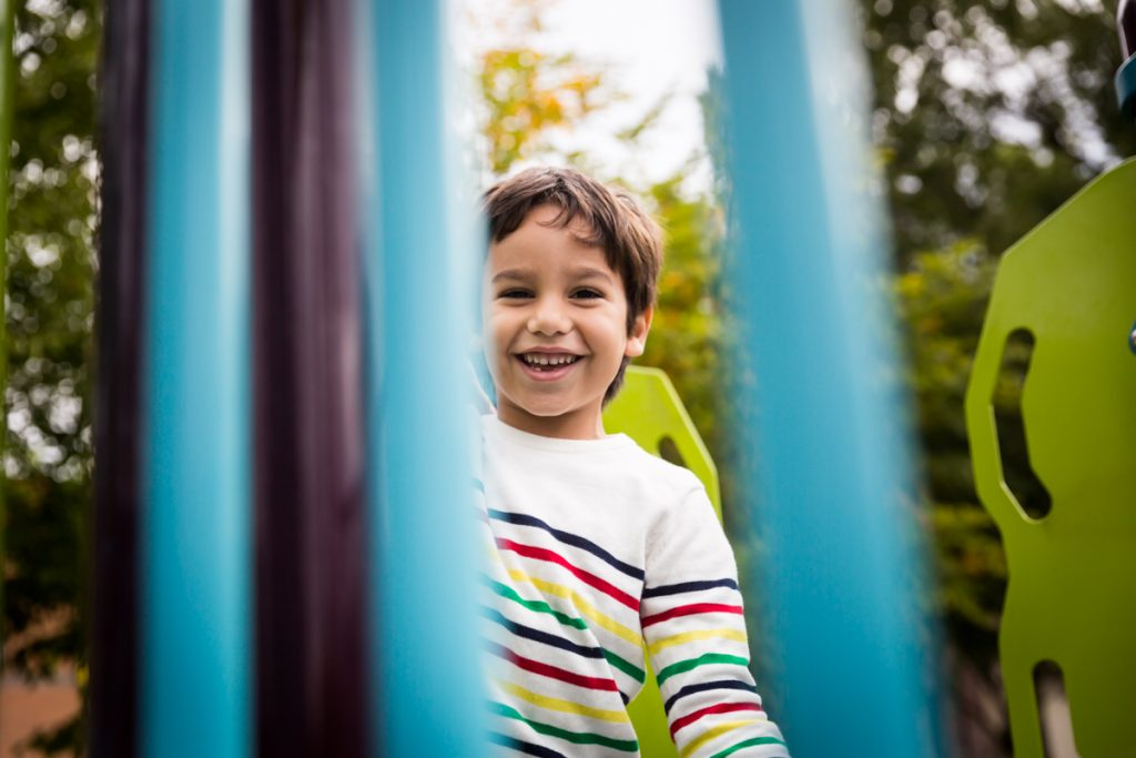 Boy looking through jungle gym bars at an Ennis Playground family portrait session