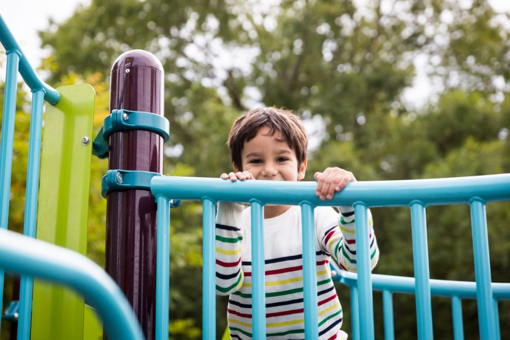 Boy holding onto railing at an Ennis Playground family portrait session