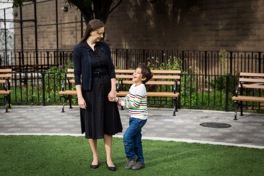 Boy laughing while holding mother's hand during a Gowanus family portrait session