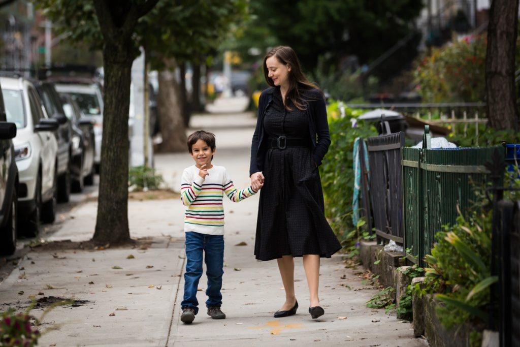 Mother and son walking down Brooklyn sidewalk holding hands