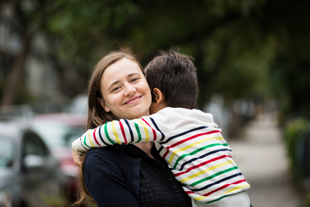 Boy hugging woman with long brown hair