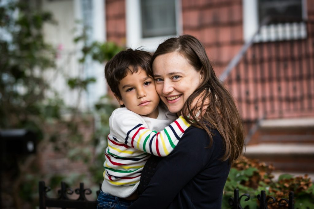 Mom and son hugging in front of house during a Gowanus family portrait session